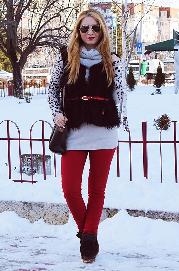 tinuta de iarna cu pantaloni rosii, pulover gri leopard, si vesta de blana neagra, ochelari de soare, tinute cu sneakers