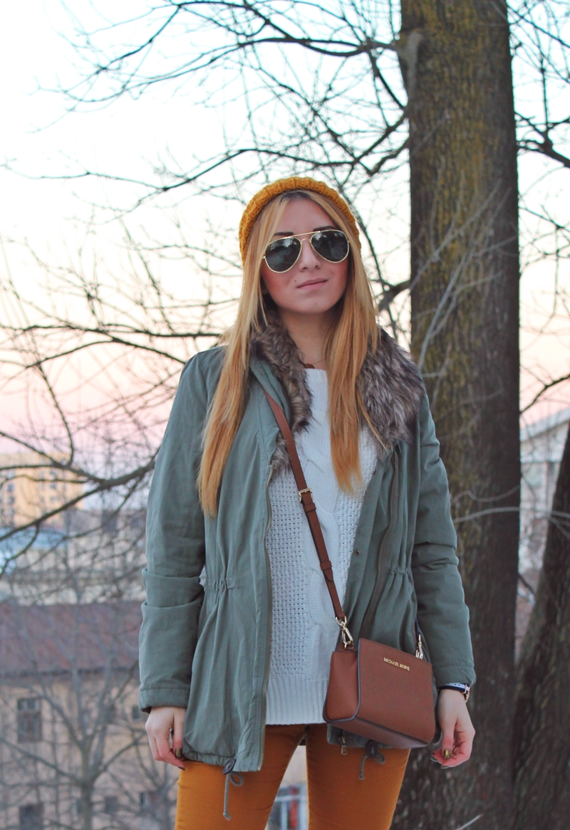 Street style winter outfit, parka and mustard pants, white sweater, sunnies