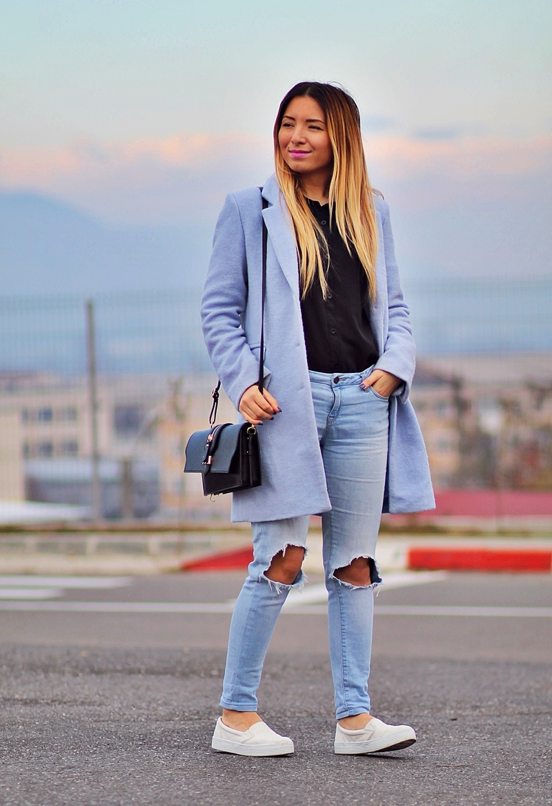 Street style - light blue coat, ripped jeans, white sneakers, black bag, black shirt