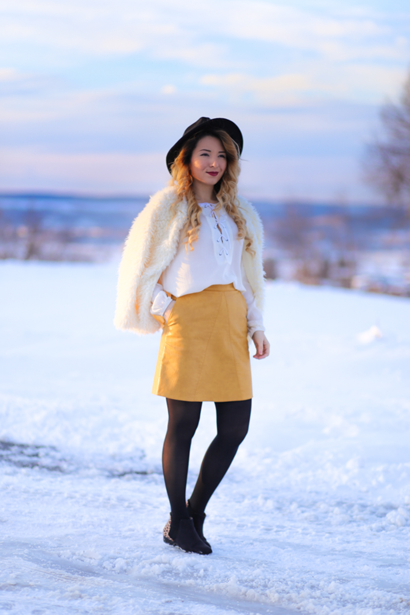 Street style: yellow a line skirt, white shirt, winter look, outfit, fluffy white coat, black hat