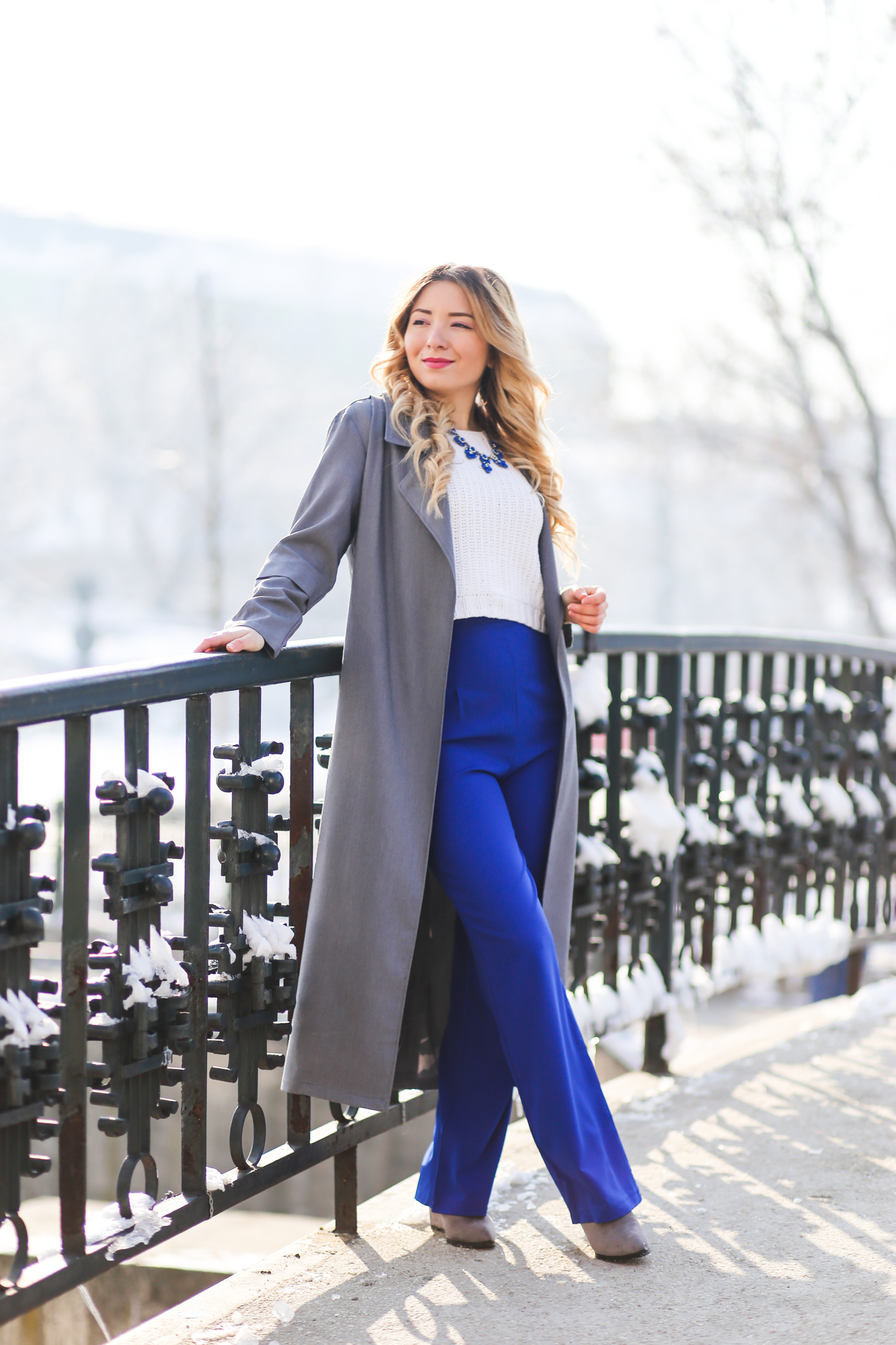 Street style: royal blue high waisted pants, white crop top sweater, grey long coat, grey boots, fashion blogger Andreea Ristea