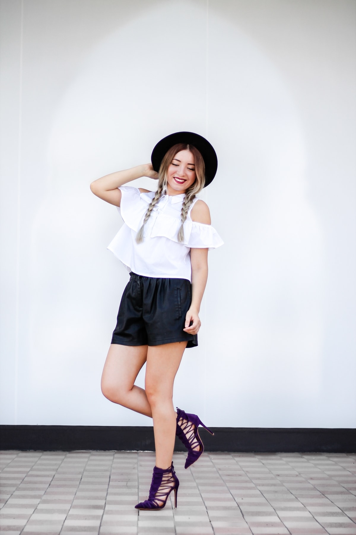 Street style: white open shoulder ruffle shirt, black leather shorts, pants, purple shoes, heels, black hat, fashion blogger Andreea Ristea, summer look
