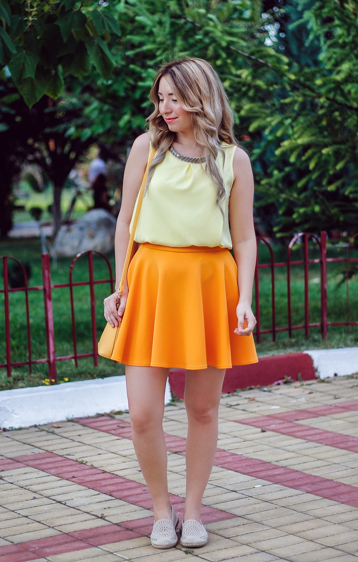 Street style: yellow top, orange skirt, yellow bag, nude shoes, tone on tone