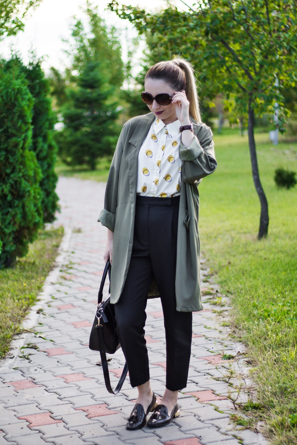 street style, 50s fashion influences, ideas, outfit, look, street style, high waisted black pants, white and yellow polka shirt, woman, military trench coat, olive moccasin, black bag, andreea ristea
