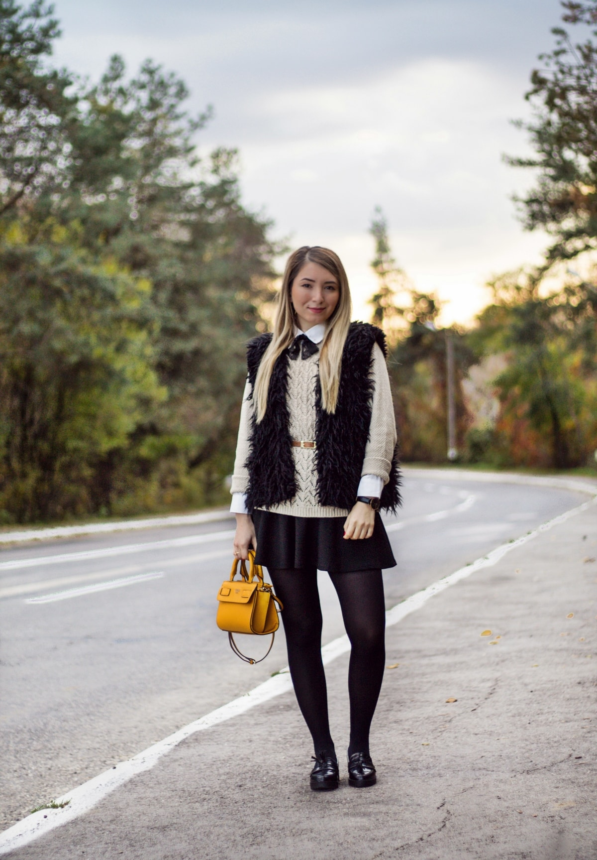 Street style, faux fur black vest, beige sweater, nude, white shirt with black bow, guess yellow bag, black loafers, black tights, autumn winter look, andreea ristea, fashion blogger, outfit of the day, ootd
