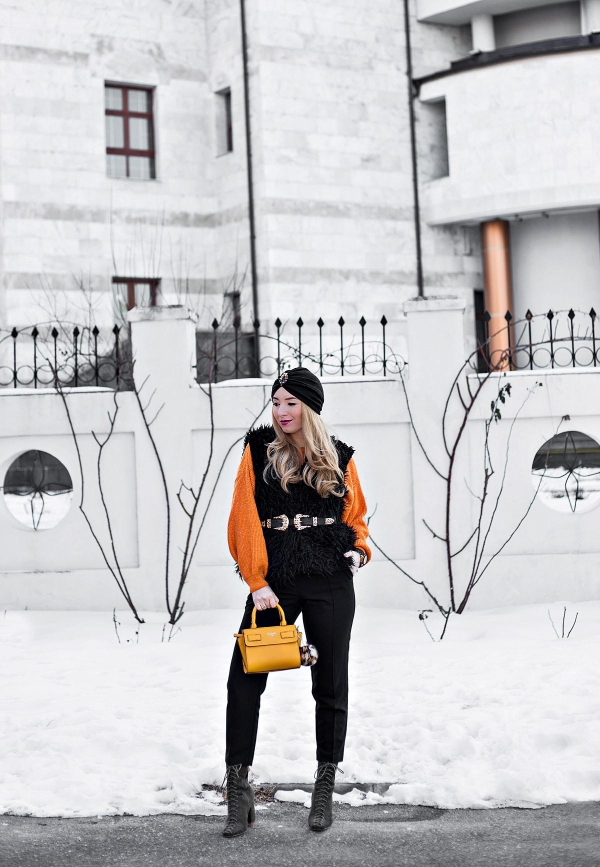 Tinuta de iarna, blogger moda, Andreea Ristea, pulover orange, portocaliu cu fir lurex, vesta blana neagra, pantaloni office negri, botine cu siret verde military, kaki, curea cu capete aurii, turban lune negru accesorizat, geanta guess, galben mustar